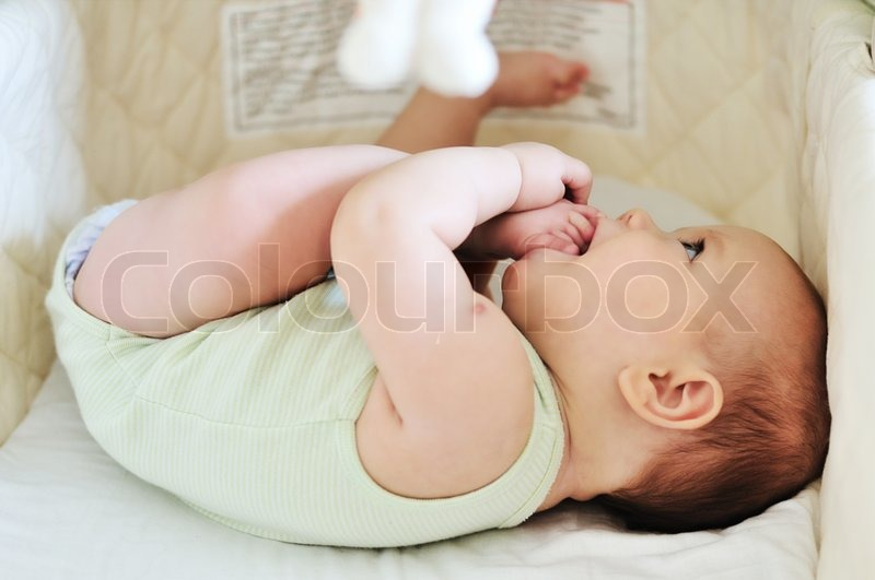Stock image of 'Baby with feet in mouth'