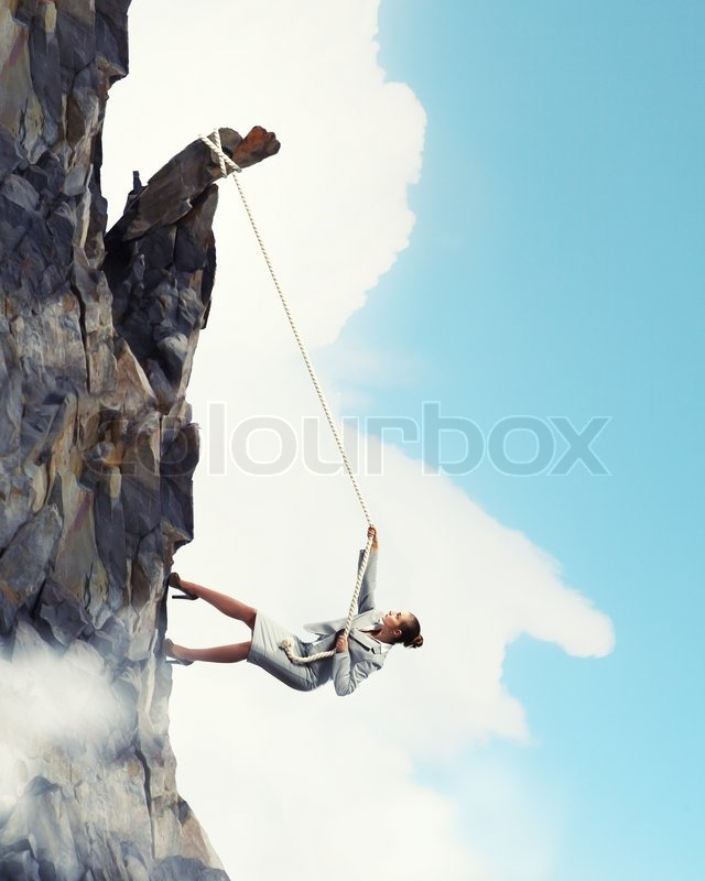 Stock image of 'Businesswoman climbing mountain'
