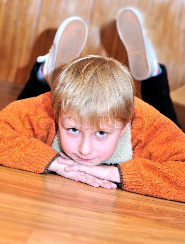 Stock image of 'Little boy laying on the wooden floor'
