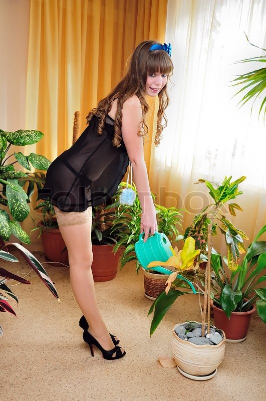 Stock image of 'Pin-up girl watering flowers'
