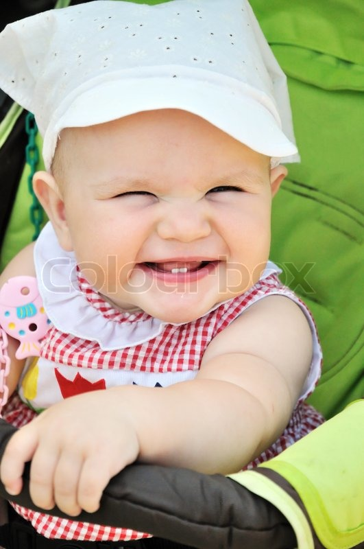 Stock image of 'smiling baby girl sitting in the stroller'