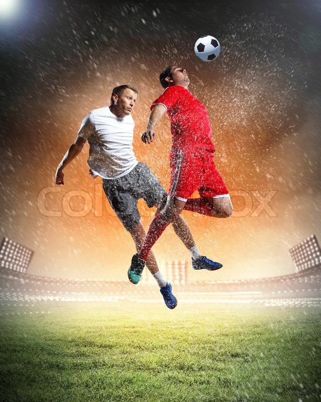 Stock image of 'Two football players striking the ball'