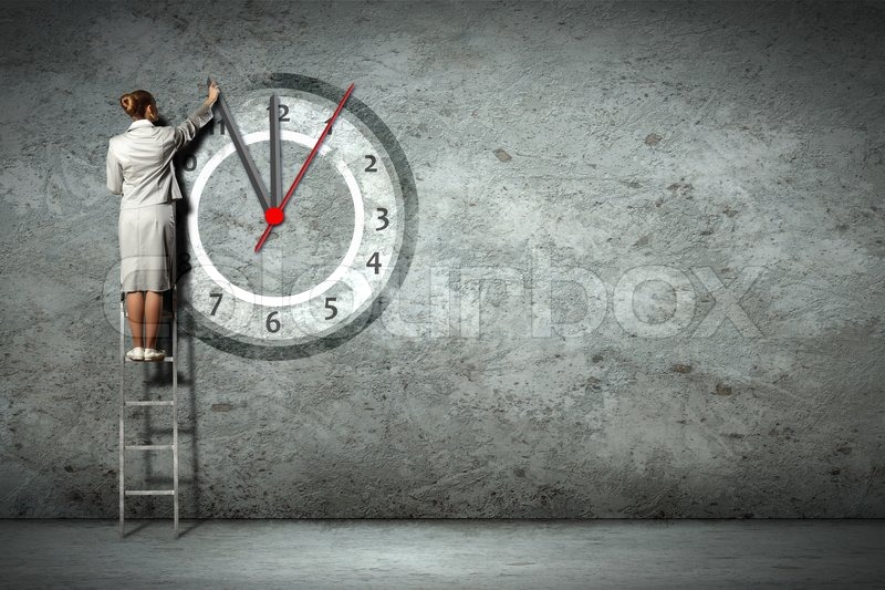Stock image of 'Businesswoman standing on ladder moving hands of clock'