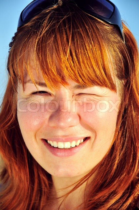 Stock image of 'sun shining  on a face of redheaded girl'