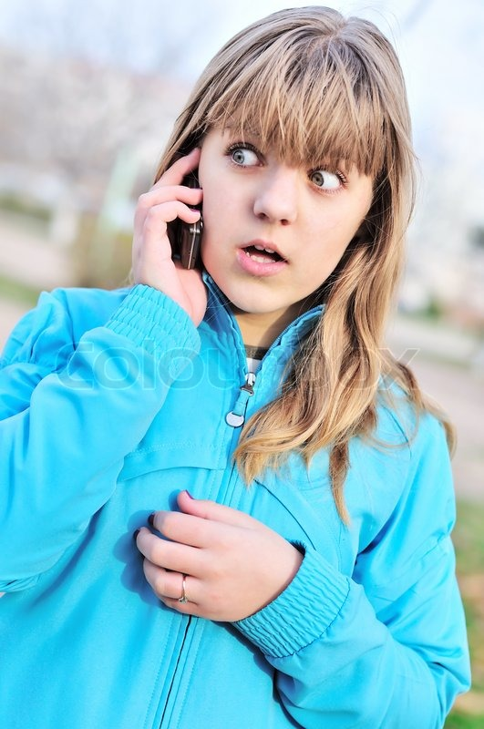 Stock image of 'Beautiful surprised teenager girl talking by cellular phone'