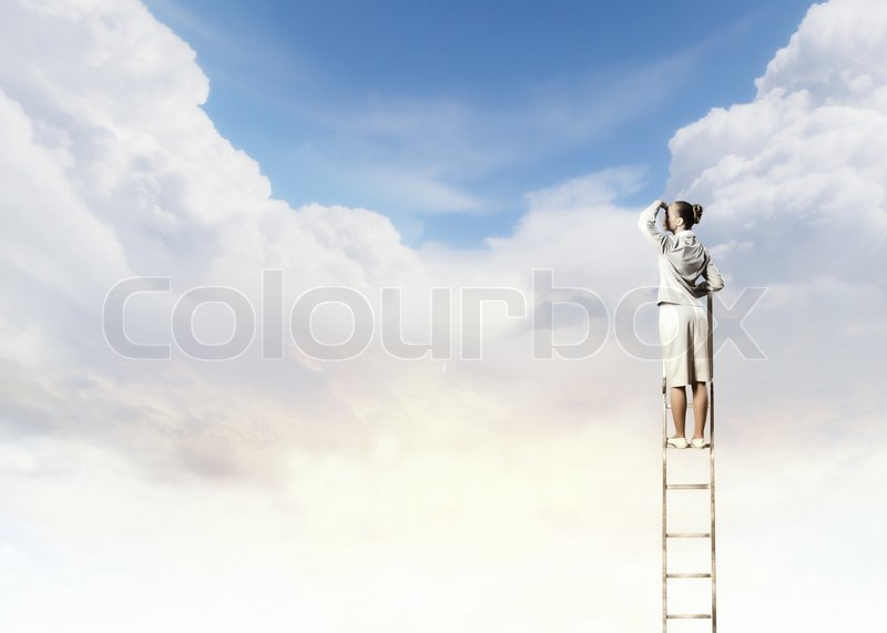 Stock image of 'Businesswoman standing on ladder'