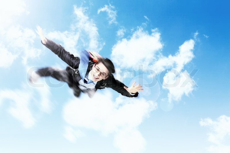Stock image of 'Young businessman flying with parachute on back'