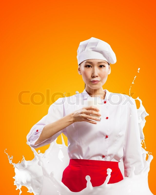 Stock image of 'Asian female cook against milk splashes'
