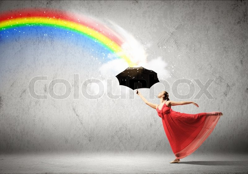 Stock image of 'Ballet dancer in flying satin dress with umbrella and a rainbow'
