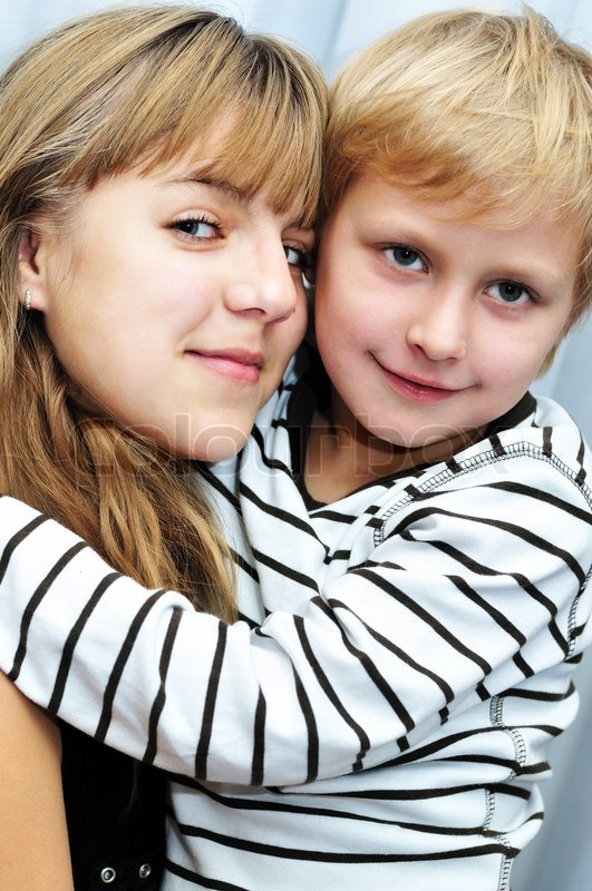 Stock image of ' Brother and sister at home smiling and embracing '