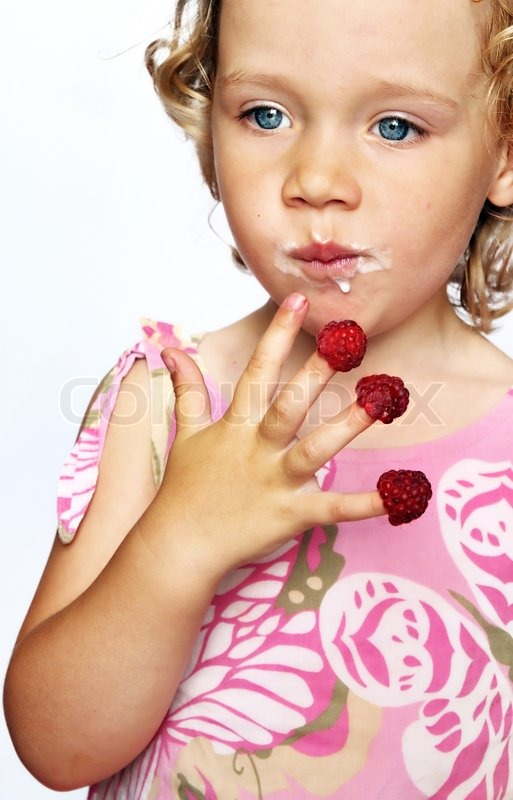 Stock image of 'Funny young girl enjoying a fresh raspberries stacking on her fingers'