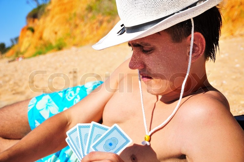 Stock image of 'Man plying cards on the beach'