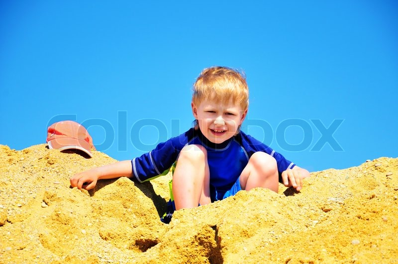 Stock image of 'Boy sitting in the huge pile sand'
