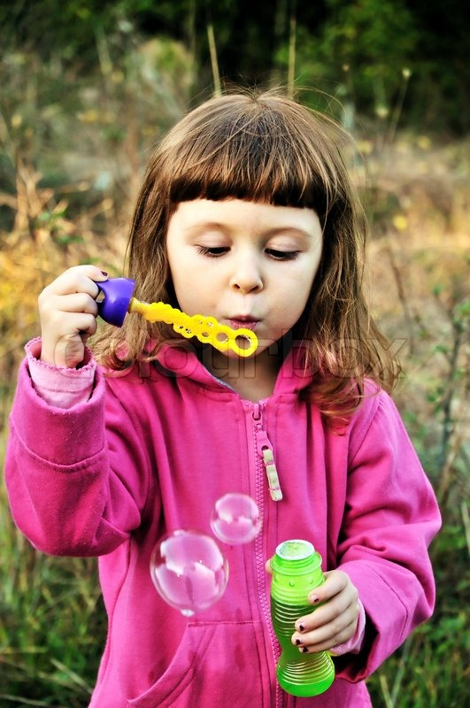 Stock image of 'little girl blowing soap bubbles in autumn forest '