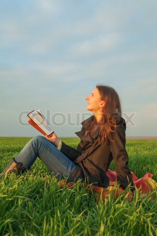 Stock image of 'Teen girl reading the Bible outdoors'