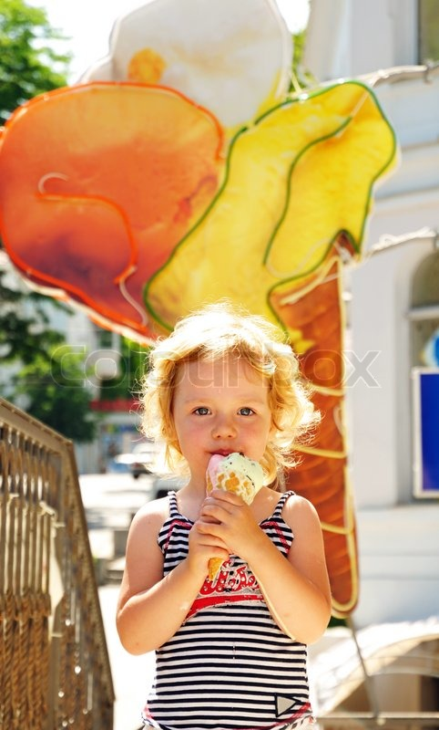 Stock image of 'little funny blonde girl eating big ice cream'