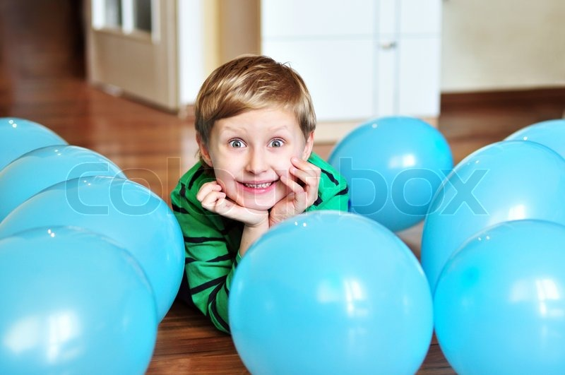 Stock image of 'Boy laying with balloons'