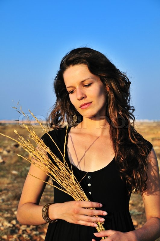 Stock image of 'Girl holding dry spikelets'