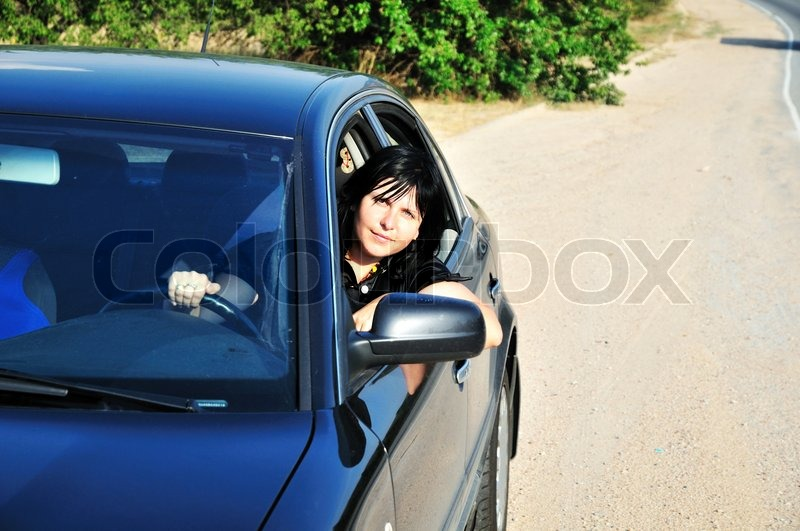 Stock image of 'young brunette woman driving a blue car'