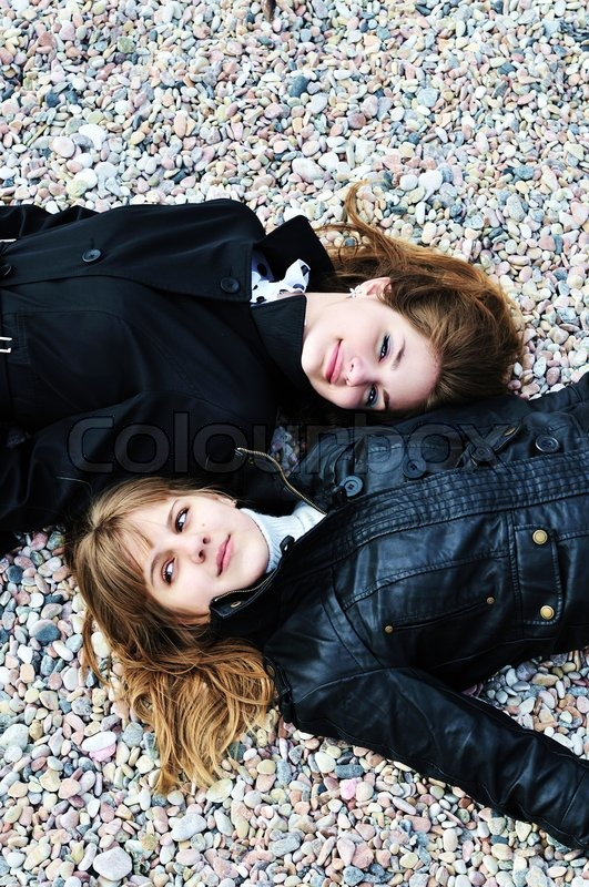 Stock image of 'Two teen girls laying on the pebble'