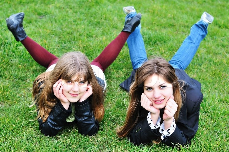Stock image of 'Two teen girls laying on the grass'
