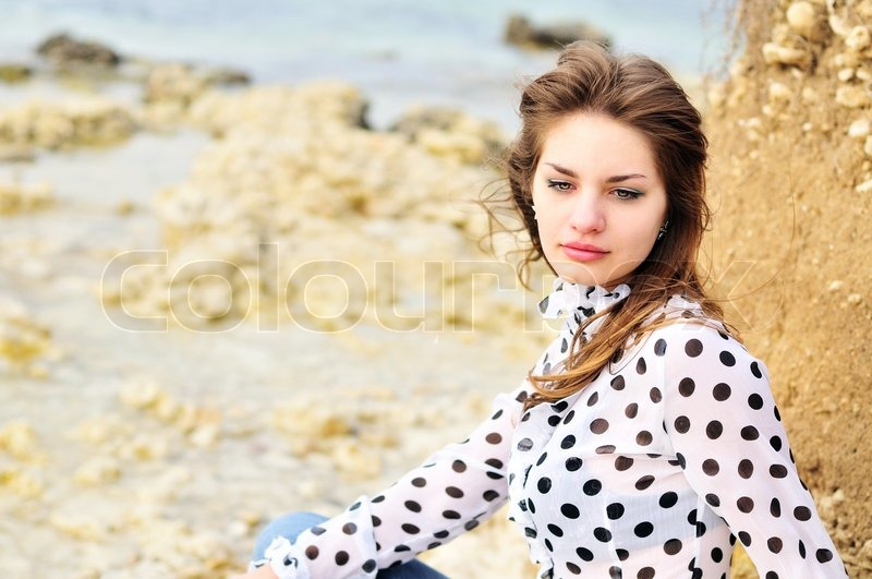 Stock image of 'teen romatic girl wearing spotted blouse on the sea coast'
