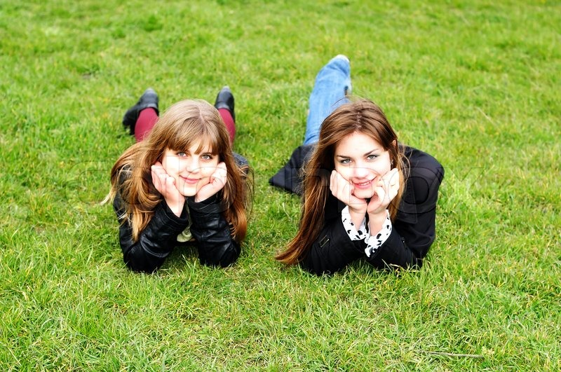Stock image of 'Teen girls laying on the green grass'