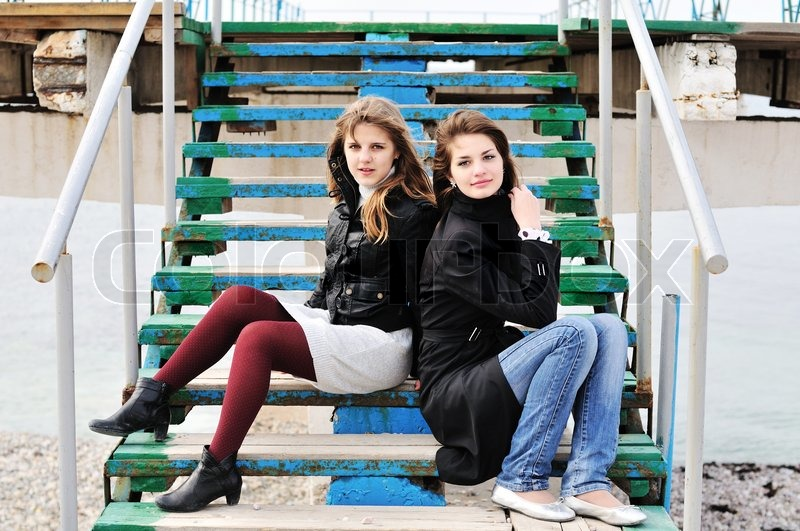 Stock image of '  two teen lovely girls sitting on  the stairs '