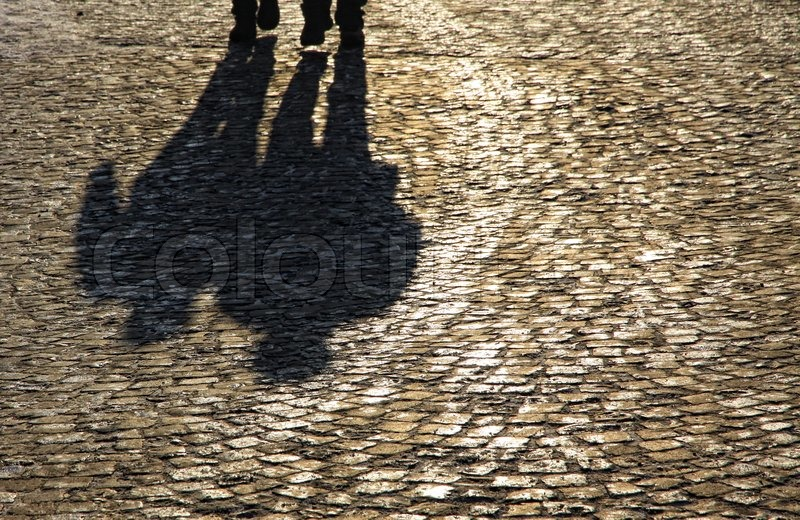 Stock image of 'Silhouette and shadows of people walking on brick pavement'