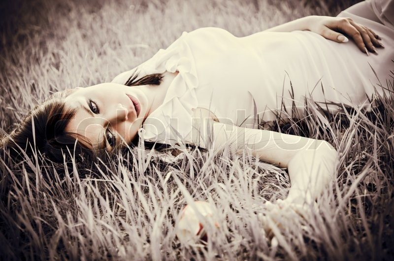 Stock image of 'Sad beautiful girl lying on grass Faded effect'