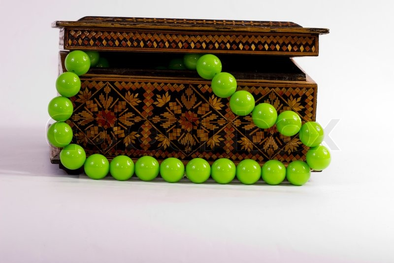 Stock image of 'Old wooden box inlaid with green and round beads'