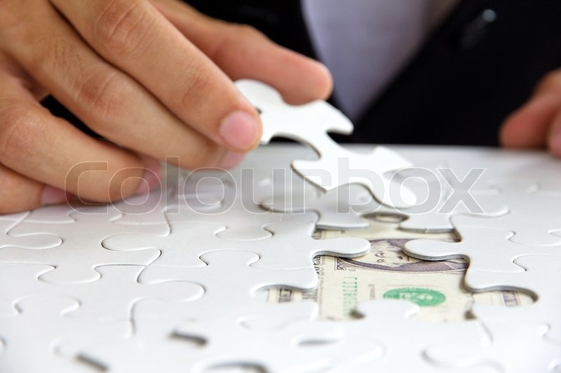 Stock image of 'Business man hand holding a puzzle piece, money concept'
