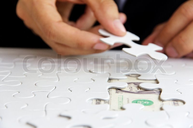Stock image of 'Hand holding a puzzle piece, green space concept'