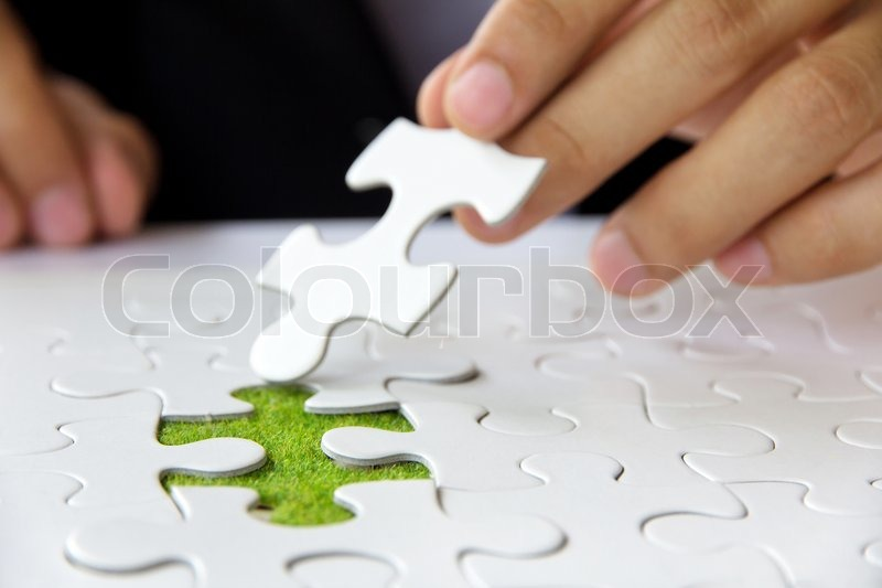 Stock image of 'Hand holding a puzzle piece'