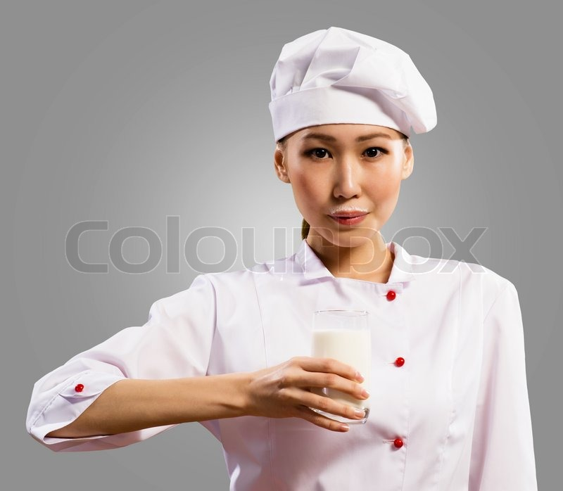 Stock image of 'Female asian chef holding a glass of milk'