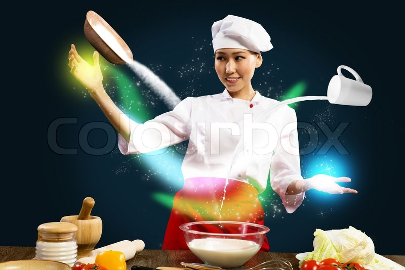 Stock image of 'Asian female chef in the kitchen conjures'
