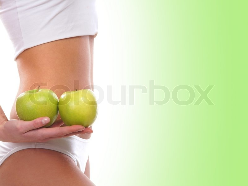 Stock image of 'Dieting concept, Beautiful belly and a fruit isolated on green'