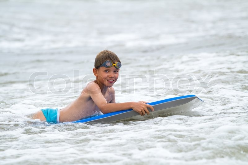 Stock image of 'Young child with a bodyboard on the beach'