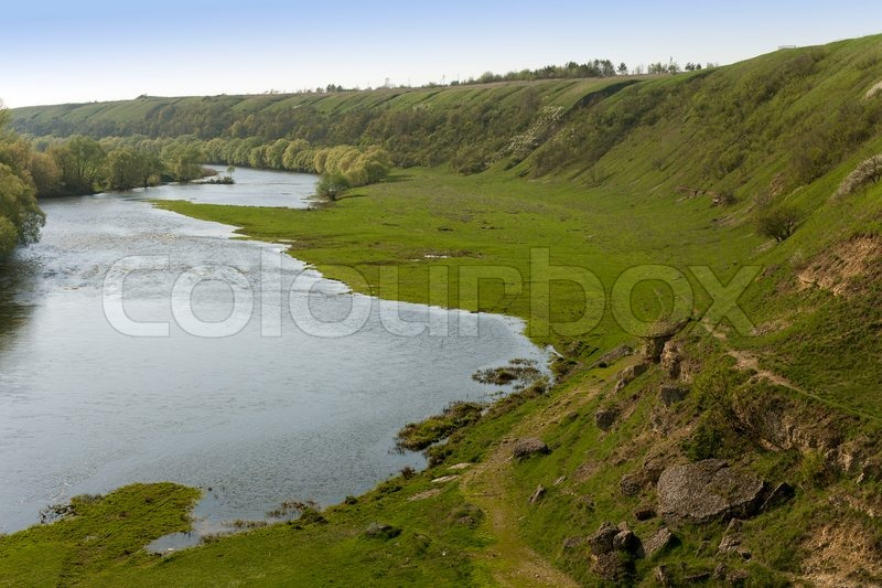 Stock image of 'River with meadow and green hill'