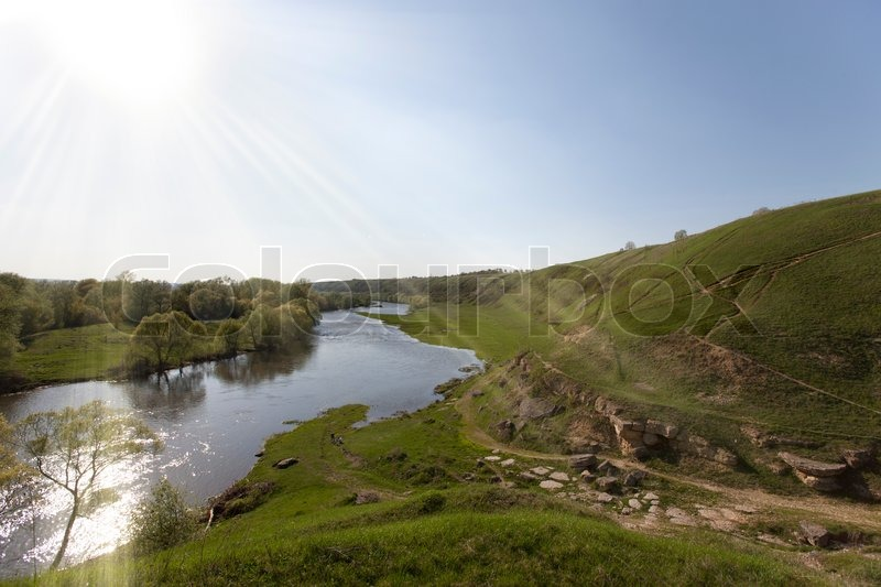 Stock image of 'Sunlight over the river and hill'