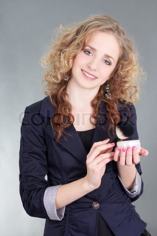 Stock image of 'Make up artist with brush and powder over grey'