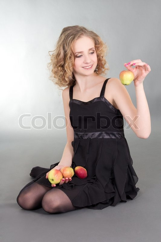 Stock image of 'Young blond sitting with apples'