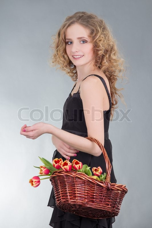 Stock image of 'Young woman with basket of flowers'
