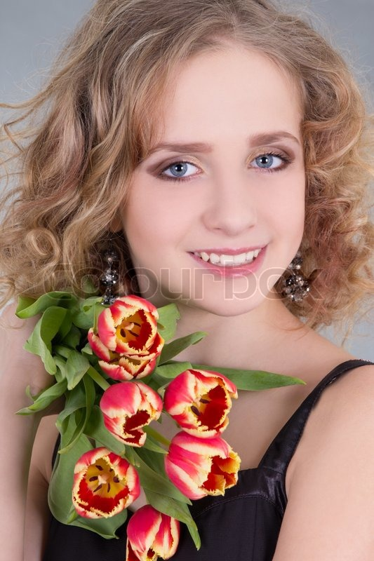 Stock image of 'Close up portrait of young woman with flowers'