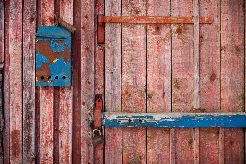 Stock image of 'old mailboxe on an old wooden door painted red'