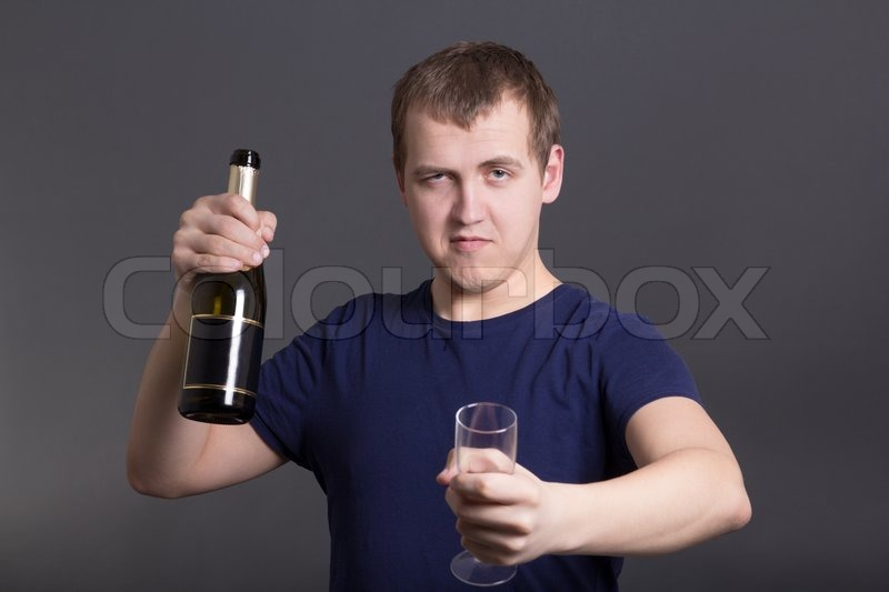 Stock image of 'Young drunk man with bottle of champagne and glass'