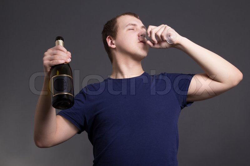 Stock image of 'Young man drinking champagne over grey background'