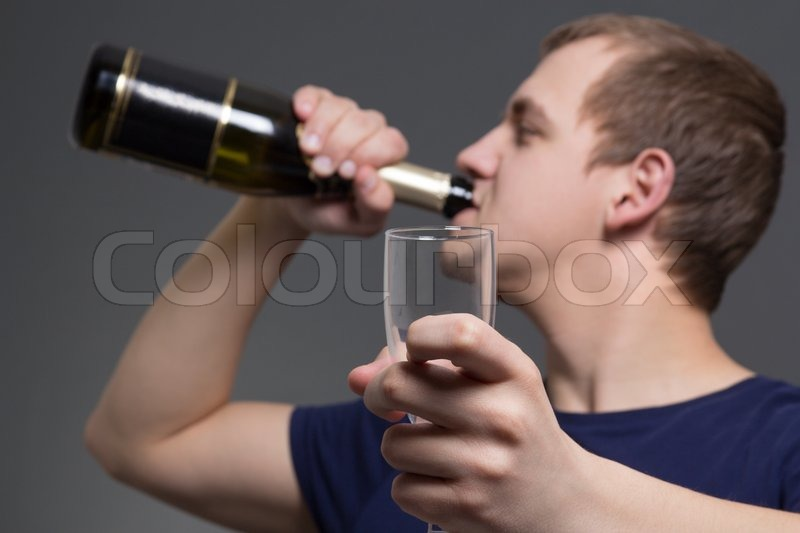 Stock image of 'Young drunk man with bottle of alcohol and glass'