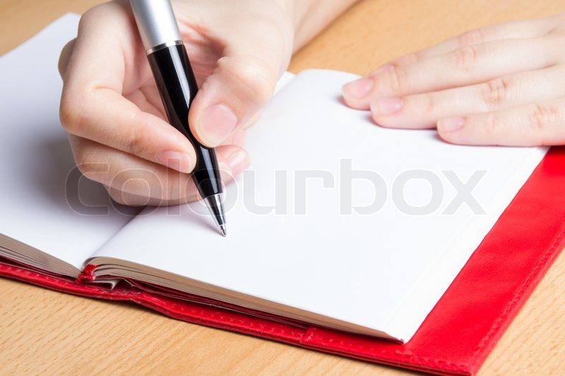 Stock image of 'hand of young woman taking notes in notebook'
