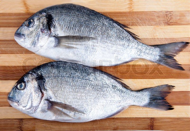 Stock image of 'Two fresh sea bream on a cutting board'